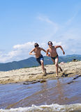 Boys run in water Stock Photo