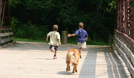 Boys Running. And dog chasing after Stock Photos