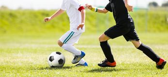 Boys Running After the Ball on Green Grass. Footballers in White and Black Shirts. Children Kicking Soccer Ball. Youth Kids Football Action. Boys Running After royalty free stock photos