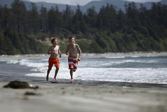 Boys running at a beach Stock Image