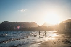 Boys running on the beach in the sunset. Summer vacation time, two kids running on the beach, sunset time, mountains on background in Calpe, Spain Royalty Free Stock Photos