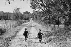 Boys running down a country farm road on the farm. Done in black and white Stock Image