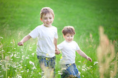 Boys running  through field Stock Images