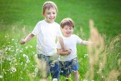 Boys running through field. Two cute preschool brothers holding hands and running through field of long grass royalty free stock photo