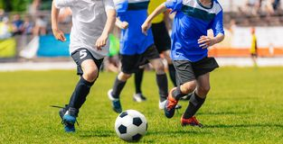 Boys running and kicking soccer ball. Close up action of boys soccer teams, aged 8-10. Playing a football match on the stadium stock images