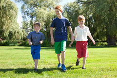 Boys running in park. A group of three boys running and walking in a park Royalty Free Stock Photo