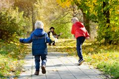 Boys running towards her mother. Autumn Park. View from the back.  Stock Image