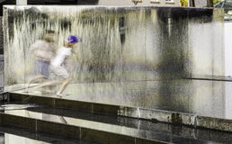 2 boys running through water. 2 boys blurred as they run through a water fountain/feature in Bristol, UK Royalty Free Stock Photo