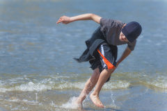 Boys runs through surf on Oregon Coast. A young boy wearing a ball cap, t-shirt,shorts and sweatshirt tied around his waist, is having a blast, running and Stock Image