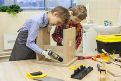 Boys with screwdrivers and drill repairing wooden stool. Two boys with screwdrivers and tools repairing wooden stool in workshop royalty free stock photo