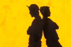 Boys Shadows Friends Differences. Boys teenagers friends back to back shadow on wall.Differences Stock Images