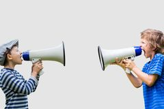 Boys shouting on megaphones while standing against gray background. Digital composite of Boys shouting on megaphones while standing against gray background Royalty Free Stock Image