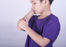 The boys are sick. Boys checking his arm with muscle pain Royalty Free Stock Photos