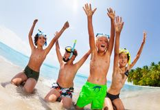 Boys sit on the beach in scuba masks lift hands. Four boys sit on the beach in scuba masks with lifted hands and screaming happy expressions smiling royalty free stock images