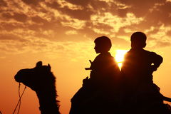 Boys sit on camel Royalty Free Stock Images
