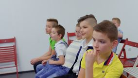 Boys sits at chairs in the room. And smiling. Children watches film. Prores codec. Camera in motion stock video