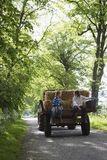 Boys Sitting On Back Of Trailer On Country Lane Stock Photo