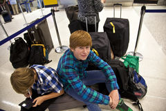 Boys is sitting on the baggage waiting for check i Stock Photos