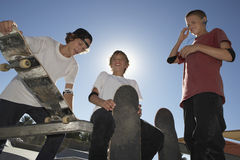 Boys With Skateboards Smiling Against Blue Sky Stock Images