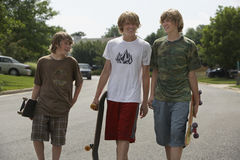 Boys With Skateboards Walking On Street Royalty Free Stock Images
