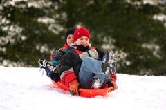 Boys Sledding. Two Boys smiling happy having a good time sledding Stock Images