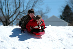 Boys sledding. Two boys sledding down a snow covered hill Stock Photo