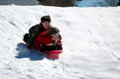 Boys sledding. Two boys sledding down a snow covered hill Stock Image