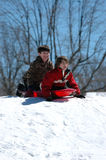 Boys sledding. Two excited boys at the top of a snow covered hill on a sled about to take off Royalty Free Stock Images