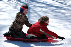 Boys sledding. Two excited boys arriving at the bottom of a snow covered hill Royalty Free Stock Image