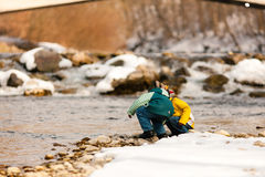 Boys in snow on river in Winter Stock Image