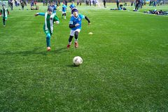 Boys soccer player speed run to shoot ball to goal on green grass. A scene of a boy`s football match. Ball soccer in kid. Ball soccer in kid football players stock photography