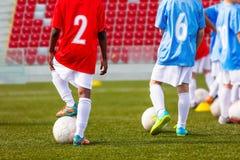 Boys soccer team training. Soccer football players training. Kids playing soccer on a stadium field stock photos