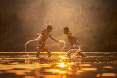 Boys splashing in water at dawn