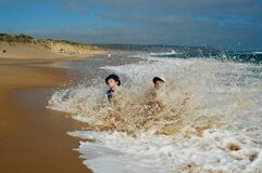 Boys splashing in waves