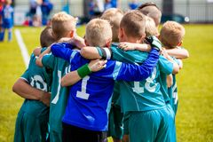 Boys` sports team huddling. Children playing sports in a team. Team sports for kids. Children sports football soccer team