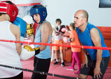 Boys sportsmans at boxing workout with instructor Royalty Free Stock Photo