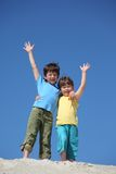 Boys stand on sand and lifted hands in greeting Stock Photography