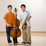 Boys standing with cello and saxophone Royalty Free Stock Photography