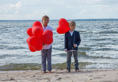 Boys standing with red heart balloons at sea shore Royalty Free Stock Image