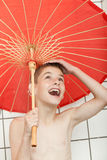 Boys standing in shower under umbrella Stock Images
