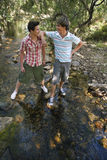 Boys Standing By Stream In Forest Stock Photo
