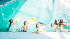 Boys starts simming in pool with plank. Children in water with are doing swim exercise. Sportive kids activity in modern sport center with pool. Healthy and Stock Photos