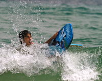 A boys struggles riding the waves. A 10 years old multi ethnic boy struggles through the waves on a surf board Royalty Free Stock Photography