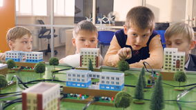 Boys studying the principles of electric power distribution. Boys are studying a small model of a city and its electric power distribution stock video