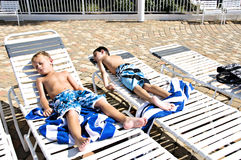 Boys Sunbathing. Two little boys sunbathing lying in lounge chairs by a pool Stock Images