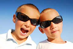 Boys with sunglasses. Outdoor portrait of two caucasian boys wearing black sunglasses in front of blue sky background Royalty Free Stock Photos
