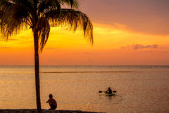 Boys at sunset on Caribbean island. Boy watches brother on kayak during sunset on Caribbean island of Cozumel, Mexico royalty free stock image