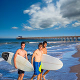 Boys surfers group coming out from beach Royalty Free Stock Image