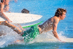Boys surfers surfing running jumping on surfboards Stock Photos