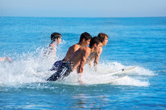 Boys surfers surfing running jumping on surfboards Royalty Free Stock Photos